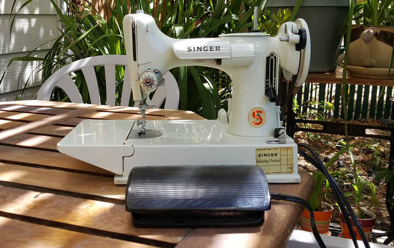 A white sewing machine with its equipment