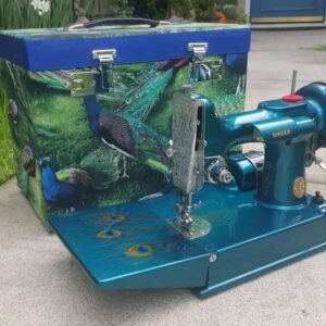 A blue sewing machine with peacock prints
