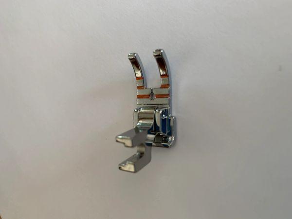 A metallic part ofr a sewing machine