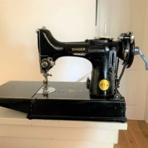 A black sewing machine on a white surface